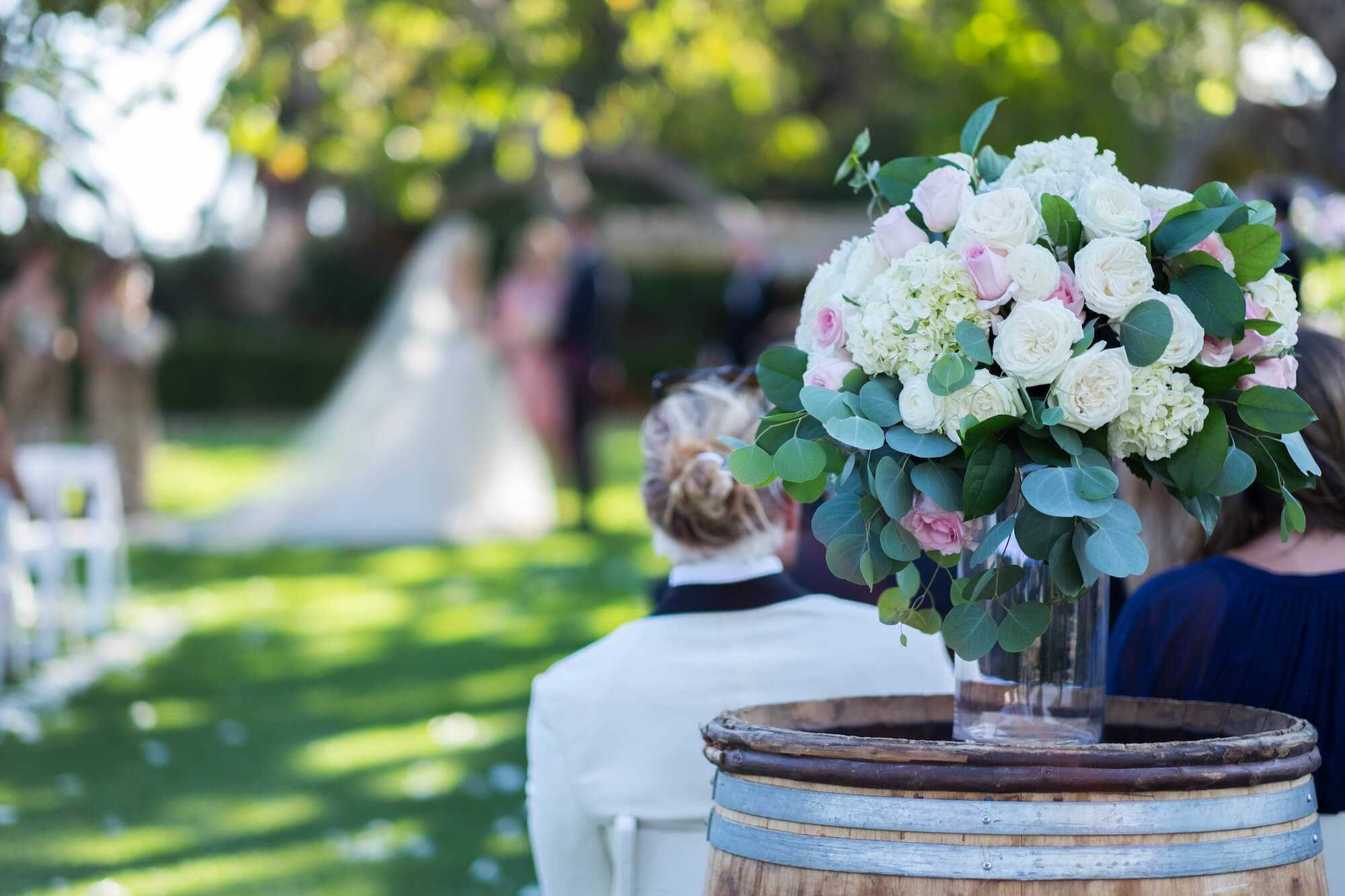 Rustic Wedding With Flower Bouquet In Vase On Barrel