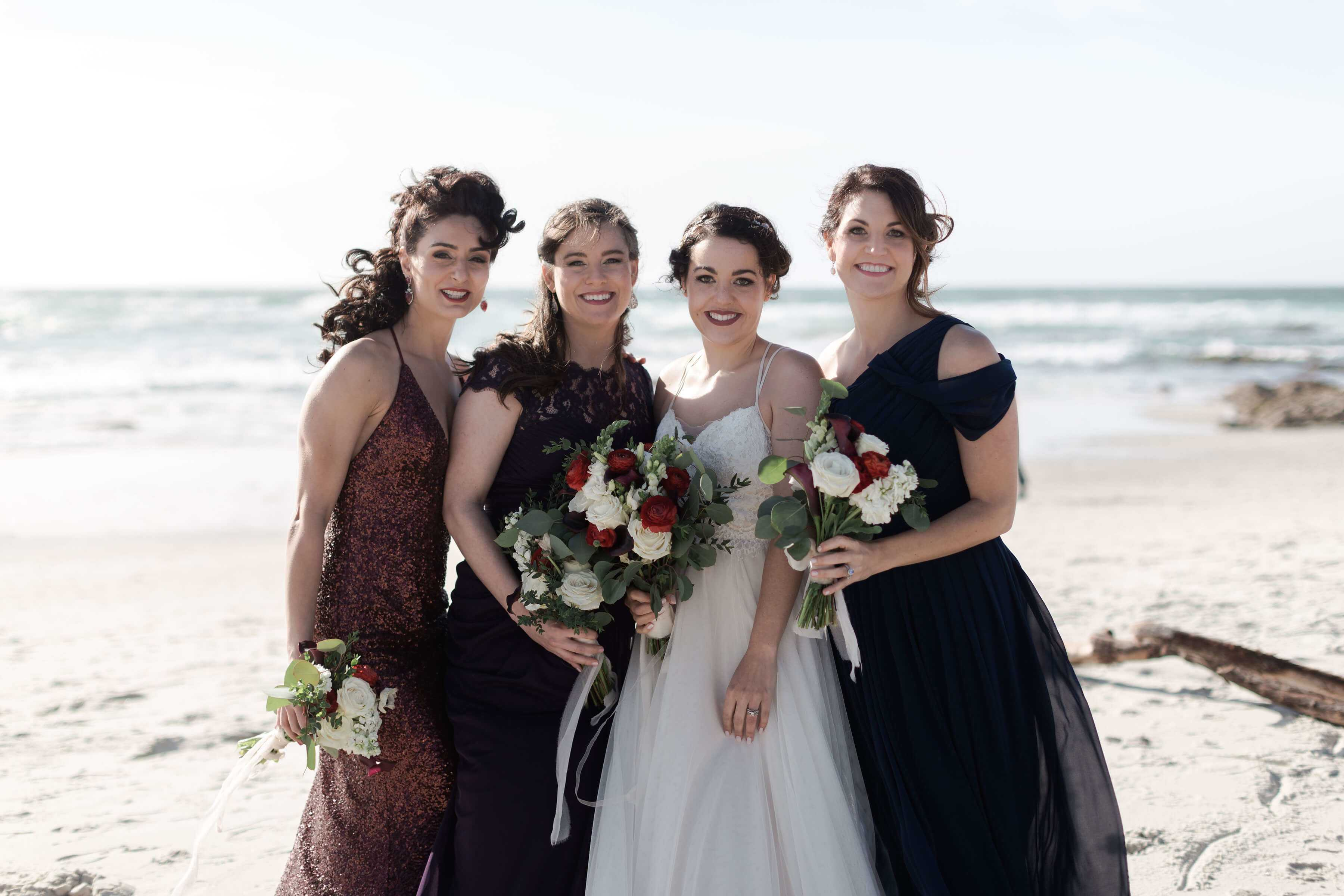 Bride And Her Bridesmaids On A Beach Holding Bouquets