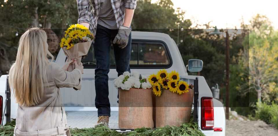 Man Giving Woman Flowers on Truck Bed