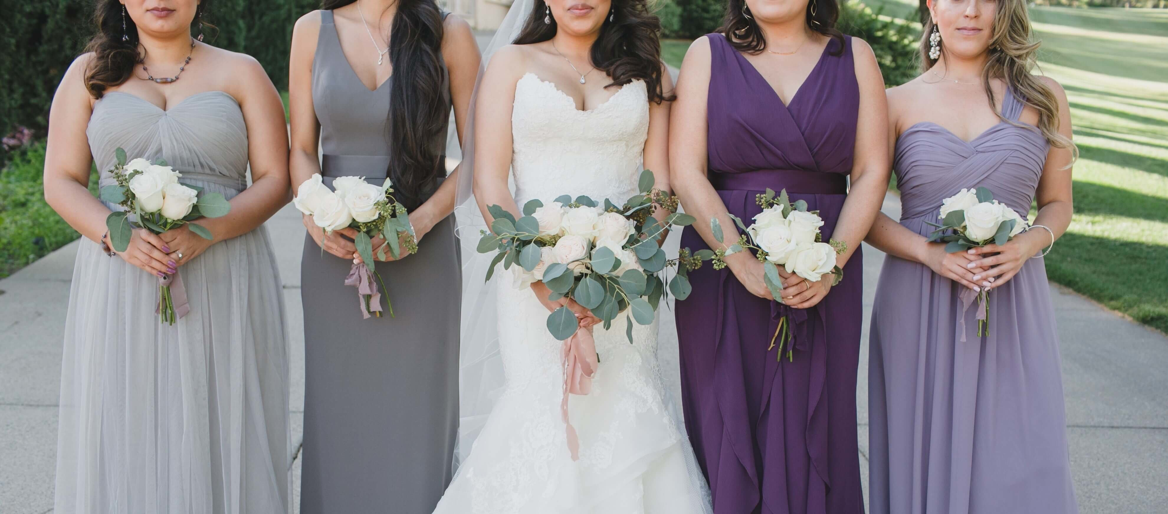 Bridal Party Showing Off Their Ivory Wedding Flower Arrangements
