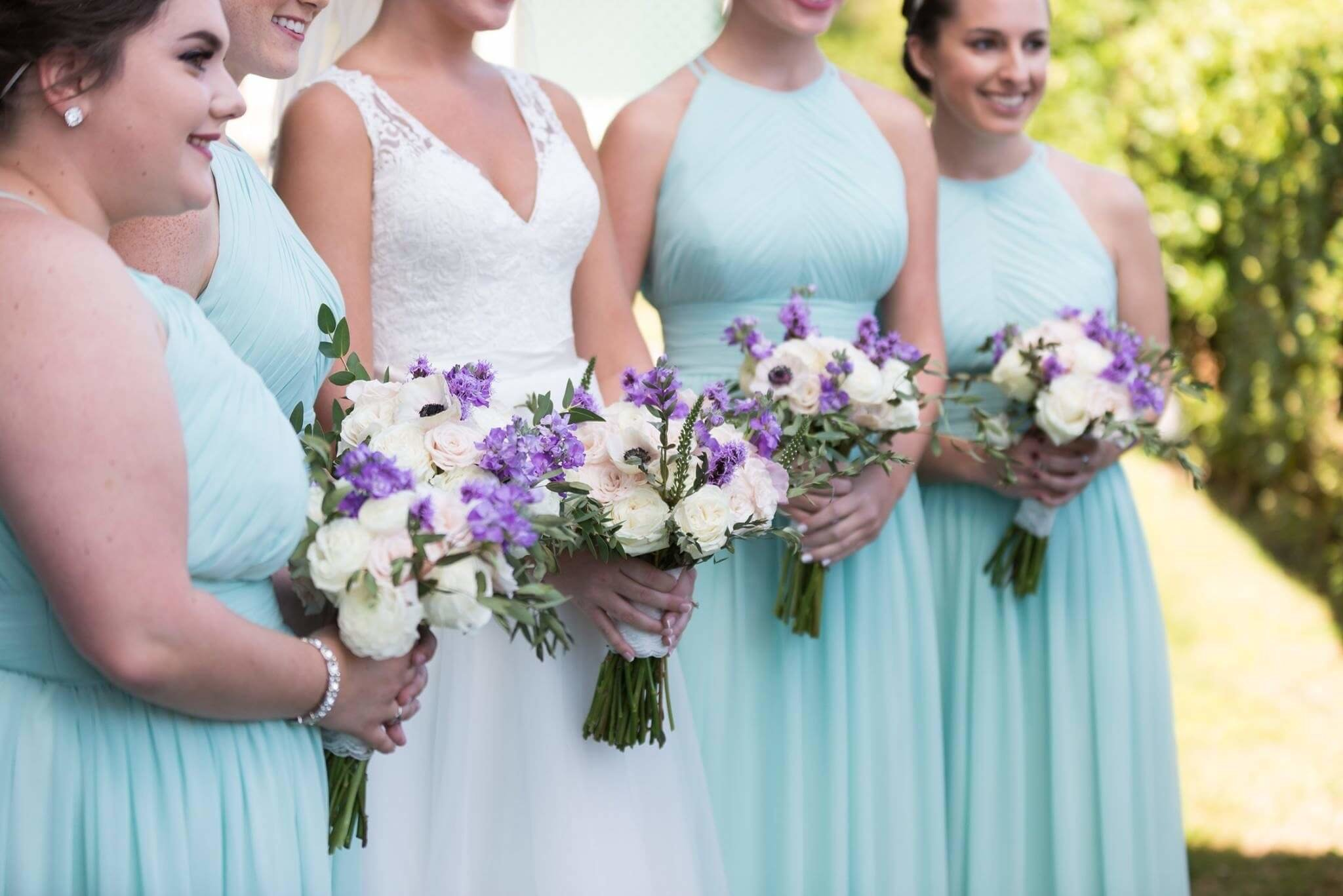 Bridal Party In Blue Holding White And Purple Flowers